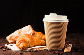 Coffee to go in a paper cup with croissants on wooden table, selective focus