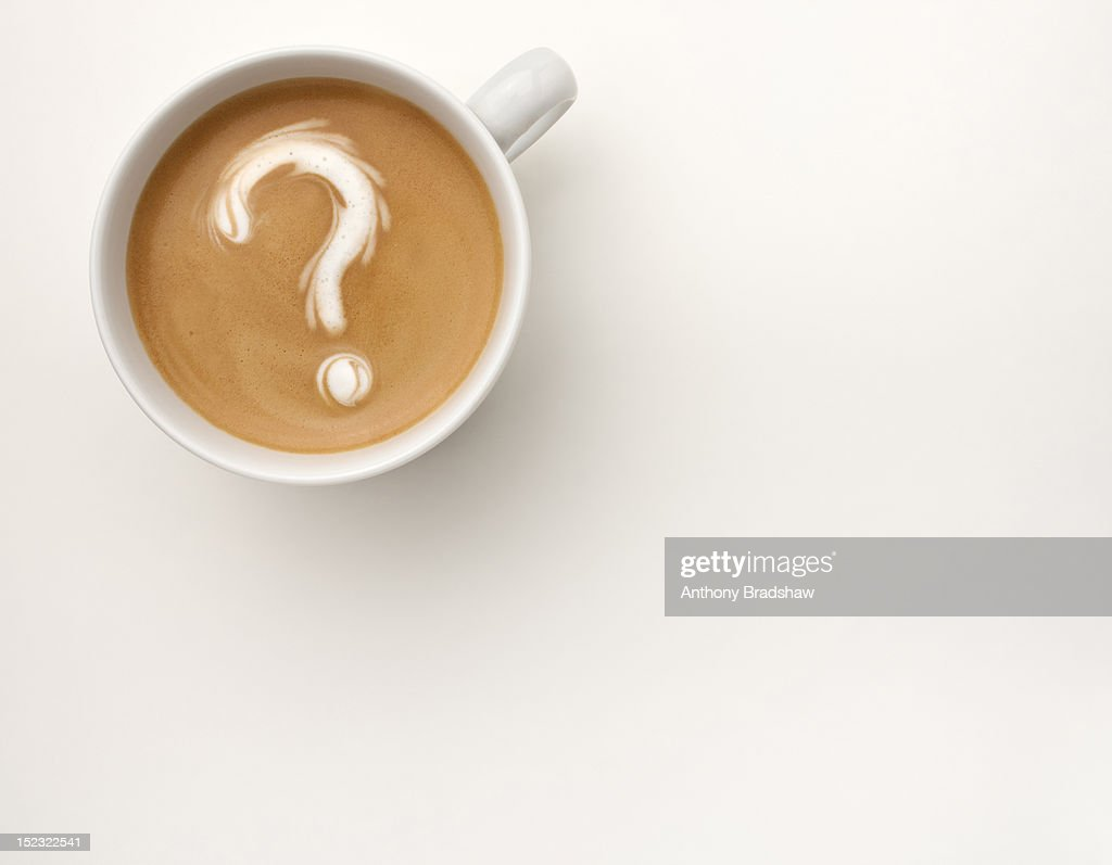 A coffee with a question mark drawn in the foam