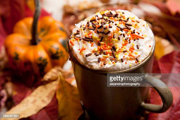 Coffee with cream and sprinkles next to a pumpkin