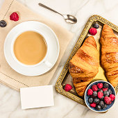 A square photo of a cup of coffee with fresh raspberries, blueberries, and croissants, with a blank business card with a place for text