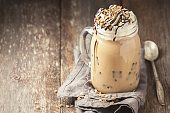Coffee with ice, cream and chocolate on wooden background