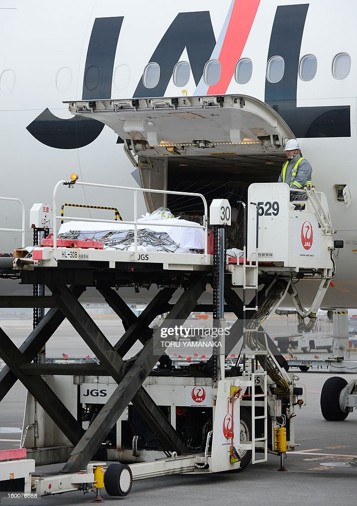 A coffin carrying the last Japanese victim of the Algerian hostage crisis is unloaded onto a cargo palette from a plane at Narita Airport, outside Tokyo on January 26, 2013