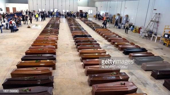 Coffin of victims are seen in an hangar of Lampedusa airport on October 5 2013 after a boat with migrants sank killing more than hundred people Italy...