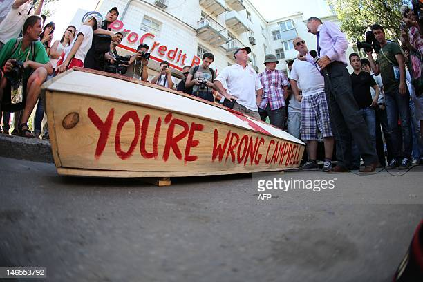 A coffin painted with a St George's Cross and with the words 'You're wrong Campbell' painted on the side by English fans sits on a street in Donetsk...