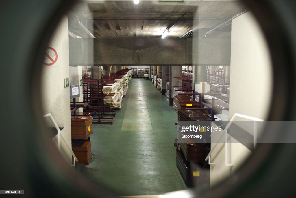 A coffin store is seen through a door window in the warehouse of the Empresa Mixta de Servicios Funerarios de Madrid SA funeral parlour in Madrid, Spain, on Monday, Dec. 17, 2012. Spain, responding to street protests and reports of suicides linked to foreclosures, introduced rules to help protect families from eviction, increasing the risk of creditor losses and weakening an already fragile banking system. Photographer: Angel Navarrete/Bloomberg via Getty Images