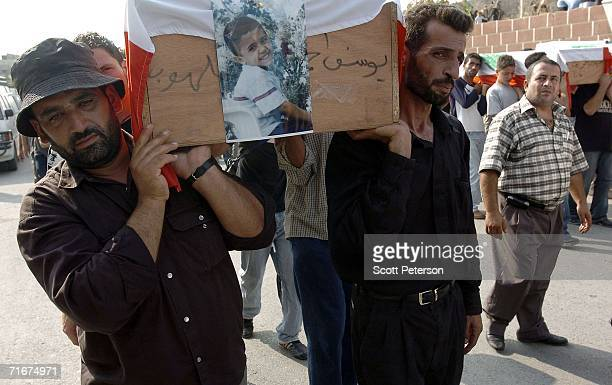 Coffins are carried in the street as most of the civilian victims of an Israeli air strike are formally buried August 18 2006 in Qana Southern...