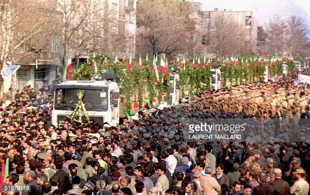 Coffins are carried on trailers through Tehran 19 February as thousands watch the funeral service of some 3000 Iranian soldiers killed during the...