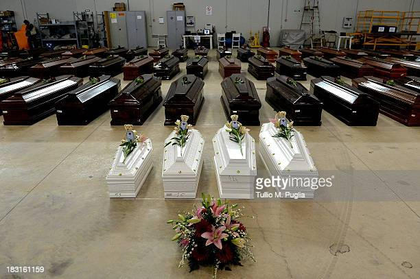Coffins of some of the African migrants including four children killed in a shipwreck off the Italian coast sit in a hangar at the Lampedusa airport...