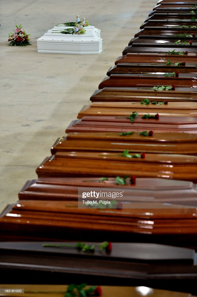 Coffins of some of the African migrants killed in a shipwreck off the Italian coast sit in a hangar at the Lampedusa airport on October 5, 2013 in Lampedusa, Italy. The search for bodies continues off the coast of Southern Italy as the death toll of African migrants who drowned as they tried to reach the island of Lampedusa is expected to reach over 300 people. The tragedy has brought fresh questions over the thousands of asylum seekers that arrive into Europe by boat each year.