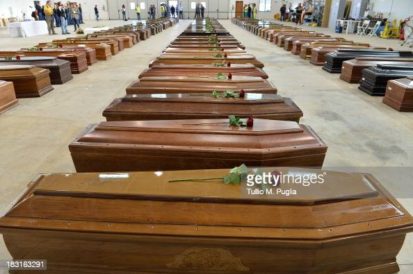 Coffins of some of the African migrants killed in a shipwreck off the Italian coast sit in a hangar at the Lampedusa airport on October 5 2013 in...