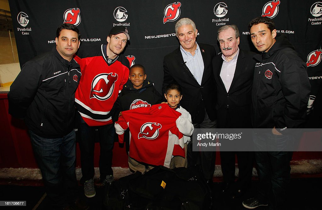 Co-founder of Hockey in Newark Keith Veltre, David Clarkson, Ty'ree Reeves, Eli Villacis, Devils owner Jeff Vanderbeek, councilman Augusto Amador and co-founder of Hockey in Newark Dennis Ruppe pose for a photo during the Hockey in Newark instructional clinic on February 13, 2013 in Newark, New Jersey.