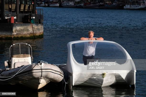 Cofounder of Sea Bubbles company Swedish Anders Bringdal stands aboard a prototype of a Bubble electric maritime 'flying taxi' during a demonstration...