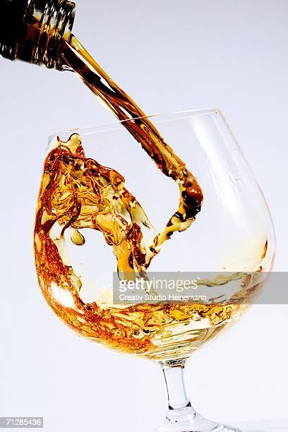 Cognac being poured into glass from bottle