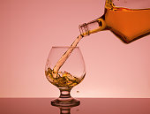 Cognac pouring from bottle into glass with splash on pink background
