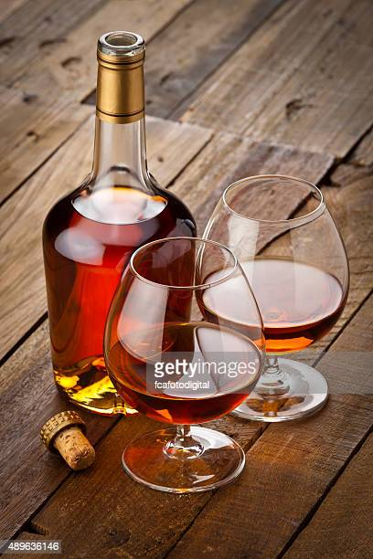 Cognac snifter with bottle on rustic wood table