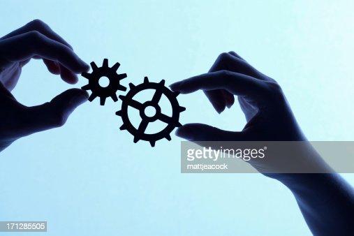 Silhueta de mãos segurando peças e engrenagens