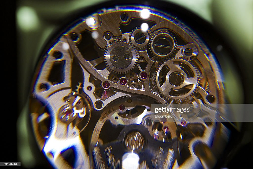 Cogs are seen through a magnifying glass on an ultra-thin mechanical self-winding Skeleton Movement 1200S Piaget luxury wrist watch, a watchmaking unit of Cie. Financiere Richemont SA, at the Salon International de la Haute Horlogerie (SIHH) watch fair in Geneva, Switzerland, on Monday, Jan. 20, 2014. Enthusiasts coveting $50,000 Cartier watches at the Swiss industry's annual fair bumped opening meetings to resolve the three-year-old Syrian civil war out of the lakeside town. Photographer: Gianluca Colla/Bloomberg via Getty Images