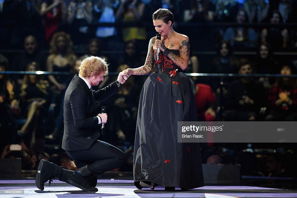 Cohost musician Ed Sheeran kneels to his cohost actress Ruby Rose appear on stage during the MTV EMA's 2015 at the Mediolanum Forum on October 25...