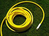 Coiled garden hose on grass, overhead view