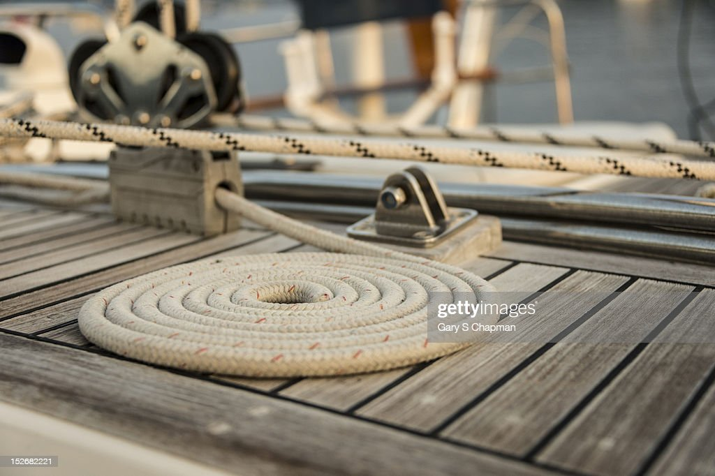 Coiled line, rope, on teak deck of 62 ft sailboat : Stock Photo