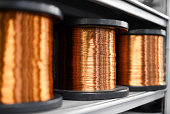 Coils of shiny copper on shelf in close up view