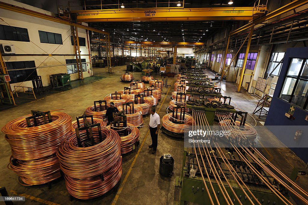 Coils of copper rod, left, stand next to freshly manufactured rod coming off the casting machine at the Luvata Malaysia Bhd. plant in Pasir Gudang, Johor, Malaysia, on Monday, May 13, 2013. At a time when copper stockpiles are rising to the highest in a decade, manufacturers are paying the biggest premiums for the metal in as much as seven years as financing deals lock up supply and extend lines at warehouses. Photographer: Munshi Ahmed/Bloomberg via Getty Images