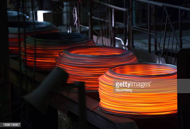 Coils of red hot wire rod cool at the Oskol Elektrometallurgical Plant steel mill operated by Metalloinvest Holding Co in Stary Oskol Russia on...