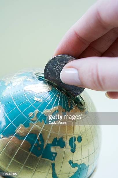 Coin being put into globe shaped money