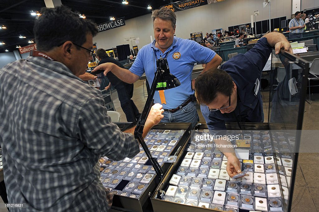 Coin dealers Gus Green, left, and Bob Campbell, in middle, and owner of All About Coins in Salt Lake City, Utah, haggle over the price of a coin. More than $1 billion of historic rare coins and colorful paper money- including $100,000 bills from the U.S. Treasury Department vaults in Washington, D.C., are on display to the public at the Nation Money Show at the Colorado Convention Center in Denver, Colorado. Dealers set up their wares today May 9th, 2012 and the show opens to the public tomorrow and runs through Saturday afternoon, May 12, 2012. Visitors can see eye-opening displays such as $2.5 million nickel, 19th century Colorado territorial gold coins, and a $500 million Treasury note amongst many other items. Many dealers and retailers from around the nation have also converged to buy and sell their own coins and money. Helen H. Richardson, The Denver Post
