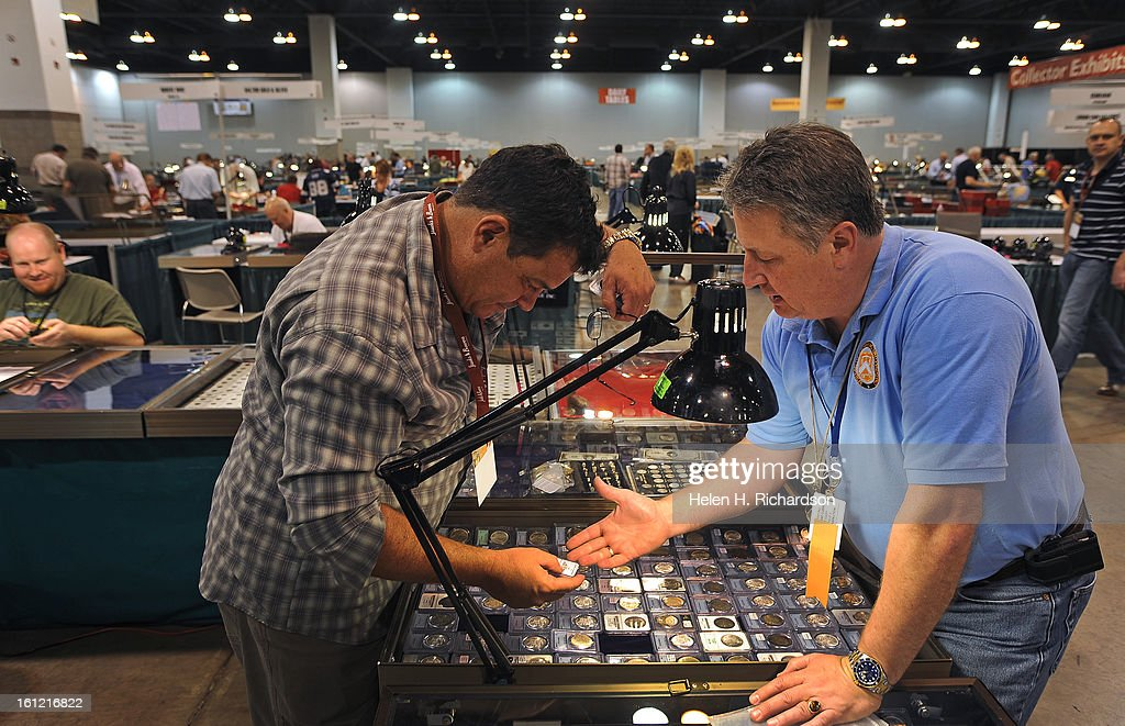 Coin dealers Gus Green, left, and Bob Campbell, right, and owner of All About Coins in Salt Lake City, Utah, haggle over the price of a coin. More than $1 billion of historic rare coins and colorful paper money- including $100,000 bills from the U.S. Treasury Department vaults in Washington, D.C., are on display to the public at the Nation Money Show at the Colorado Convention Center in Denver, Colorado. Dealers set up their wares today May 9th, 2012 and the show opens to the public tomorrow and runs through Saturday afternoon, May 12, 2012. Visitors can see eye-opening displays such as $2.5 million nickel, 19th century Colorado territorial gold coins, and a $500 million Treasury note amongst many other items. Many dealers and retailers from around the nation have also converged to buy and sell their own coins and money. Helen H. Richardson, The Denver Post