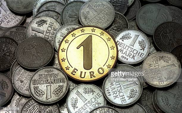 EURO coin lying on a pile of 1 DM coins