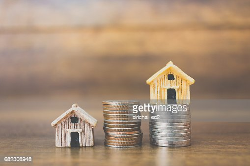Coin money and house model on wooden background : Stock Photo