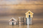 Coin money and house model on wooden background , Finance and banking concept.