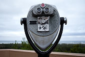 Coin operated binoculars with Pacific Ocean sea shore forest in the background