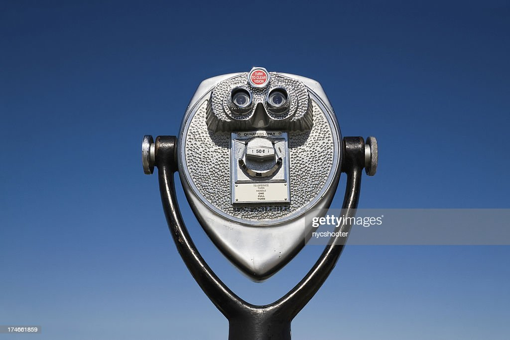 Coin Operated Binoculars set against blue sky background