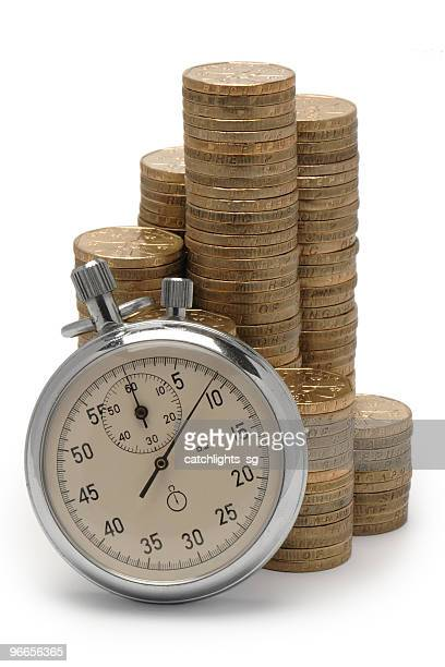 Coin pieces stacked up with an old pocket watch in front