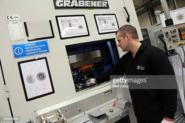 A coin press operator makes a commemorative coin for the christening of HRH Prince George of Cambridge at The Royal Mint on October 7 2013 in...