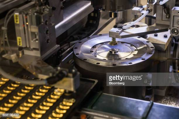 A coin press stamps gold bullion coins during their production at The Royal Mint in Llantrisant UK on Thursday March 23 2017 Britain's Royal Mint is...