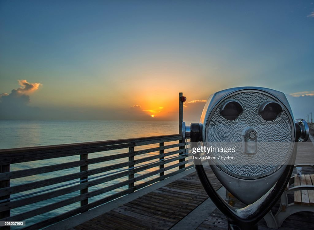 Coin-Operated Binocular On Pier Over Sea Against Sky During Sunset