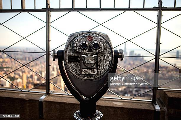 Coin-Operated Binoculars By Cityscape Against Sky