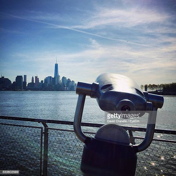 Coin-Operated Binoculars In Front Of Lake Against Sky