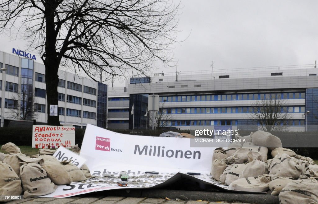Coins and Nokia mobile telephones lie besides a placard reading 'Millions' during a demonstration 24 January 2008 in front of the Nokia plant in Bochum, western Germany. More than half of Germans do not want to own a Nokia mobile telephone after the group said it would close its factory in the country, a study showed.
