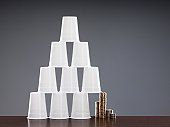 Coins holding up one side of cup pyramid