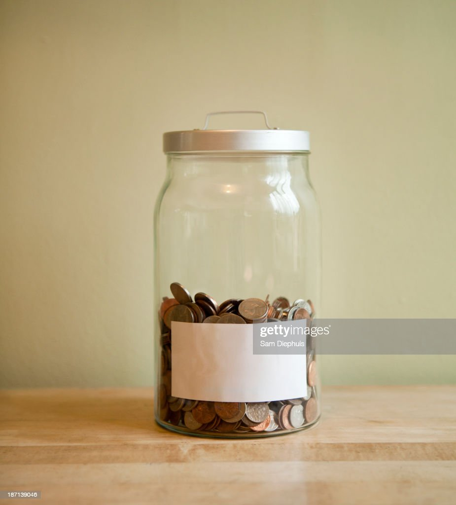 Coins in blank labeled jar : Stock Photo