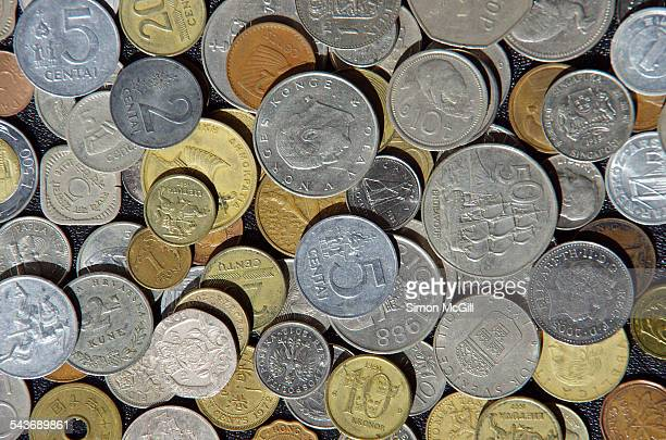 Coins some no longer legal tender from various countries spread across a black background