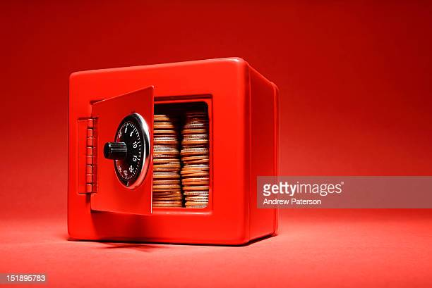 Coins stacked inside a red safe