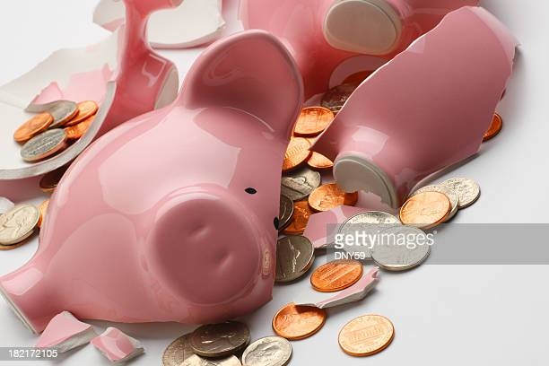 Coins strewn around broken pink piggy bank