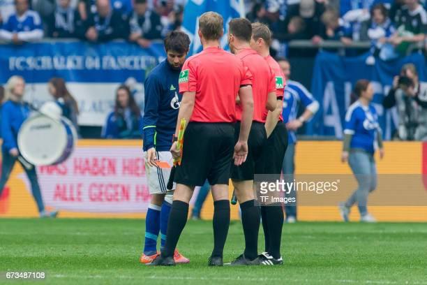 Coke of Schalke gives Referee Felix Zwayer the red card back during the Bundesliga match between FC Schalke 04 and Borussia Dortmund at VeltinsArena...