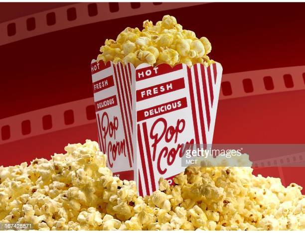 2 col x 325 inches/108x83 mm/368x281 pixels Kurt Strazdins color illustration of a box of movie popcorn set in a mound of popcorn