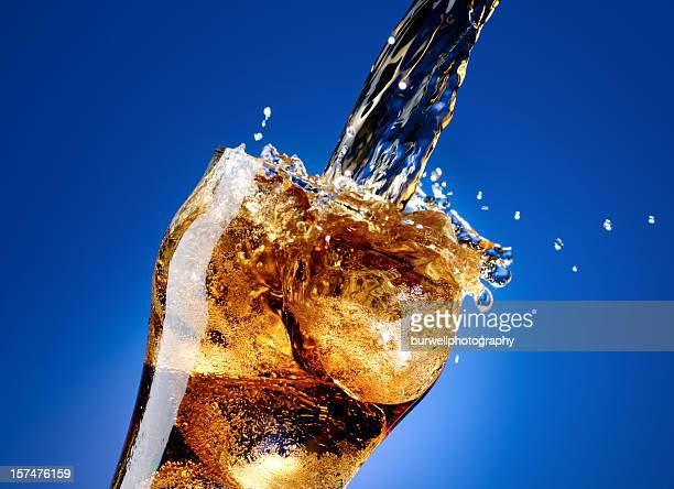 Cola with a large splash, isolated on blue
